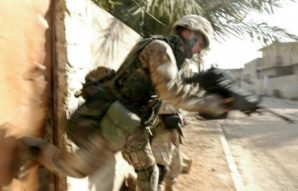 US Marine struggles to kick in a re-enforced door in Afghanistan - suspected of being a stash house for weapons.
