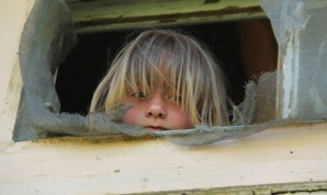 """I am concerned about the seniors and the young children that go to bed hungry, and one-half of those who get SNAP benefits, Supplemental Nutrition Assistance Program benefits, are in actuality children"""", said Rep. Jackson Lee. Pictured here: Little girl looks out the window in her dilapidated low income housing project in Phoenix, Arizona."""