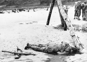 An American soldier lays dead on Normandy Beach. He was shot multiple times by a German machine gunner.