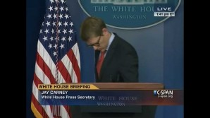 A dejected White House spokesperson Jay Carney walks off stage after explaining ObamaCare website glitches.