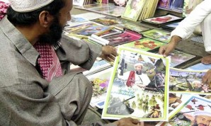 Pakistani men purchase al-Qaeda posters which are very popular in the marketplace to show support for the terrorists in Afghanistan.