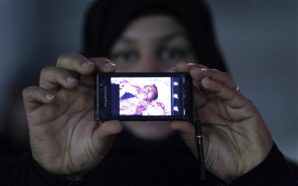 A woman shows a picture of her husband beaten and killed by the police and military security forces in Bahrain.
