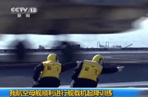 Chinese ground crew guides fighter jet takeoff on board Liaoning - China's Aircraft carrier.