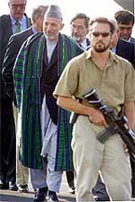 A US bodyguard walks with his machine gun in front of Afghan President Hamid Karzai (rear L) after Karzai arrived at the US Rhein Main Air Base in Frankfurt, Germany.