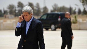 Secretary of State John Kerry on a phone as his bodyguards make sure the coast if clear and stands ready to respond in case the senior U.S before boarding a helicopter to Amman, at Mafraq air base