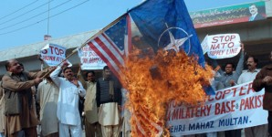 Pakistani protesters bun NATO and American flags in 2013.