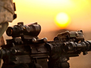 A US soldier somewhere near the border region between Afghanistan and Pakistan waits for the Taliban as the sun sets in the west.