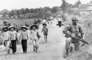1st Division soldier guarded Route 7 as Vietnamese women and children returned home to the village of Xuan Dien from Ben Cat, Vietnam, in December 1965.