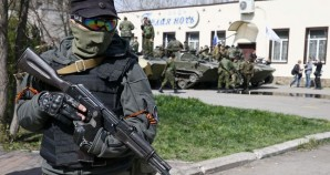 A pro Russian mercenary stands guard near armored personnel carriers.  .