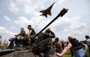 Ukrainian  tanks backed up by combat jet aircraft surround a village in eastern Ukraine, filled with terrified civilians of mostly ethic Russian?Ukrainian background.