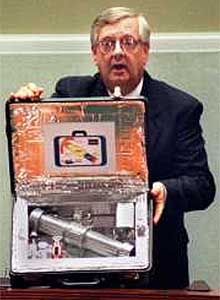 """Rep. Curt Weldon (R-Penn) holds mock-up of a hypothetical """"suitcase"""" nuclear bomb during a hearing on Russian espionage chaired by Rep. Dan Burton (R-Indiana), 24 January 2000.•Small size (60x40x20 cm) and relatively light weight (probably upward of 30 kg). These parameters are generally consistent with available information about Soviet 152-mm artillery shells, as well as with the U.S. SADM.[19] •Low yield (less than 1 kt, maybe as low as 0.1 kt).  •Remained under control of the 12th GUMO (the Main Department at MOD in charge of handling all nuclear devices), were kept at or near MOD Special Forces (Spetsnaz) bases, as well as at central storage facilities, and were intended for transfer to Spetsnaz at short notice.  •Short life span between scheduled maintenance. According to the chief of the 12th GUMO, Igor Valynkin, small munitions required replacement of components every several months (other sources mentioned six months).[20] Valynkin's statement is the most direct corroboration of the allegations about the existence of portable nuclear devices. Stationary nuclear mines with such a short warranty period simply did not make sense, while portable devices for use behind enemy lines could still be acceptable. •Were likely equipped with reasonably sophisticated permissive action links (PALs), which should preclude unauthorized use. Also, there is unconfirmed information that some small nuclear devices (munitions for 152-mm howitzers) were kept during peacetime in """"half-assembled"""" state, i.e., parts were kept separately, although quick assembly in the case of war was possible."""