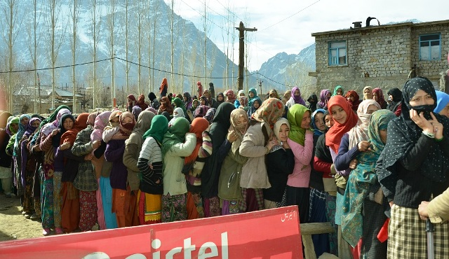 Voters stand in a queue as they wait to cast their vote at a polling station in Kargil on Tuesday