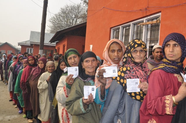 Voters stand in a queue as they wait to cast their vote at a polling station in Sonawari Kashmir on Tuesday