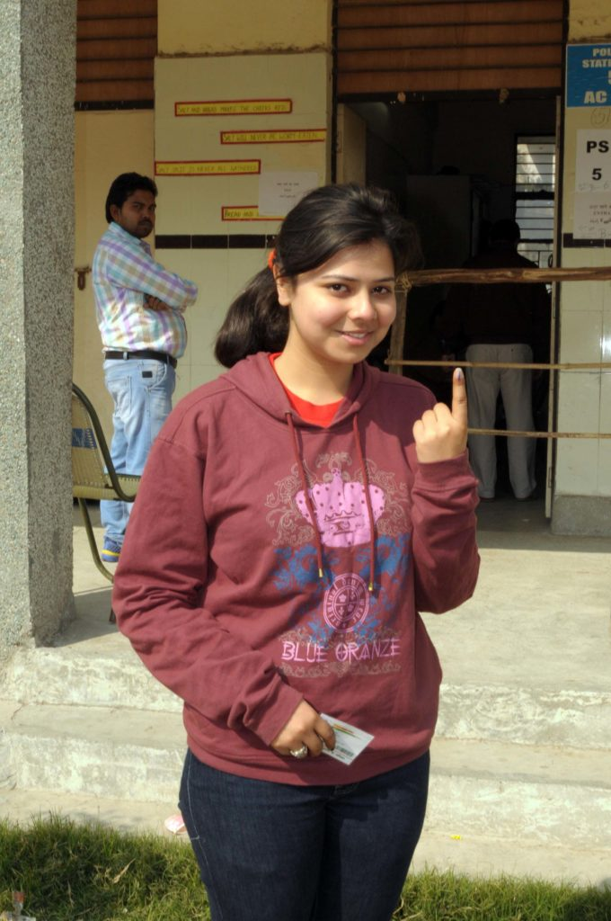 A young voter showing mark of indelible ink after casting her vote, at a polling booth, during the Delhi Assembly Election, in Delhi on February 07, 2015.