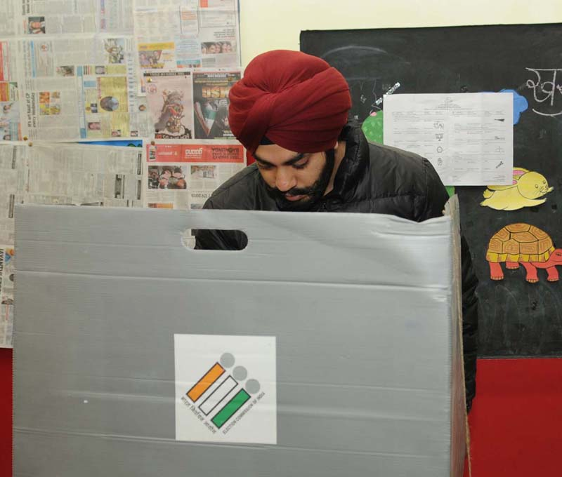 A man voter casting his vote at a polling booth, during the Delhi Assembly Election, in Delhi on February 07, 2015.