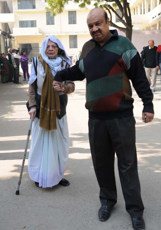 An elderly woman being carried at a polling booth to cast her vote for the Delhi Assembly Election, in New Delhi on February 07, 2015.