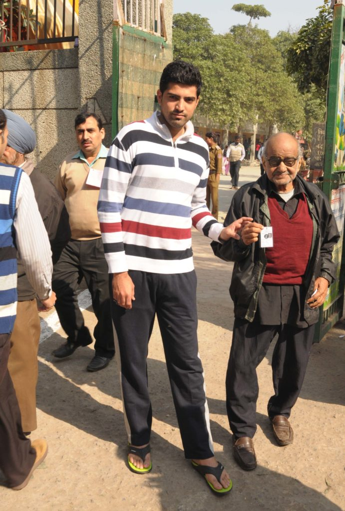 An old man being carried at a polling booth to cast his vote for the Delhi Assembly Election, in New Delhi on February 07, 2015.