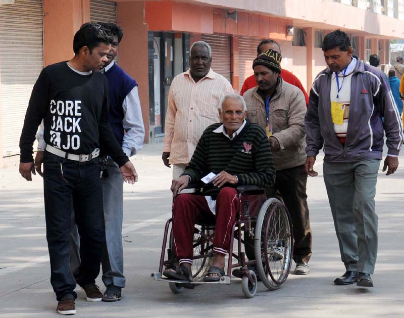 The physically handicapped voter being carried at a polling booth to cast his vote for the Delhi Assembly Election, in New Delhi on February 07, 2015.