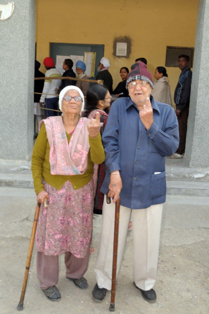 An elderly couple voters showing mark of indelible ink after casting their votes, at a polling booth, during the Delhi Assembly Election, in Delhi on February 07, 2015.