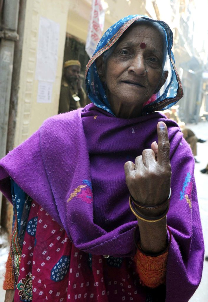 An Elderly woman voter showing mark of indelible ink after casting her vote, at a polling booth, during the Delhi Assembly Election, in Delhi on February 07, 2015.