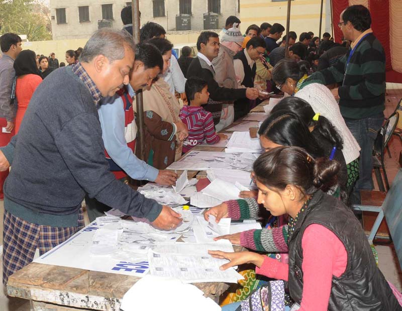 Voters identifying their name in voter list, at a polling booth, during the Delhi Assembly Election, in Delhi on February 07, 2015.