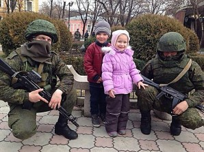 """Putin said: """"A number of Western countries imposed sanctions and restrictions on Crimea and on Russia as a whole. Our neighbours, it must be said, have not shown much inventiveness. They cut off the water supply or create other problems."""" Pictured here:  Russian troops pose with children in Crimea. Contrary to western media reports the Russian troops are seen as defenders of the people. Average citizens here don't fear the soldiers...who they know are there to protect them during the reunification process, which include massive rebuilding and investment projects. ."""