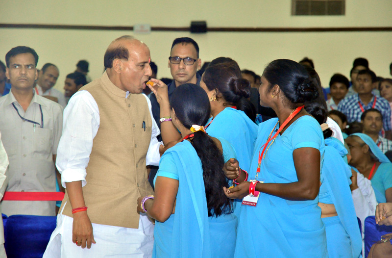 """The Union Home Minister, Mr. Rajnath Singh being offered sweets by Dalit women, during a get-together on the sidelines of the National Seminar on """"Untouchability no more"""", in New Delhi on April 13, 2015."""